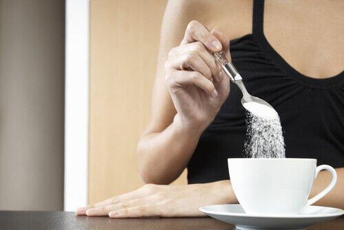 Женщина бросает сахар в чашку